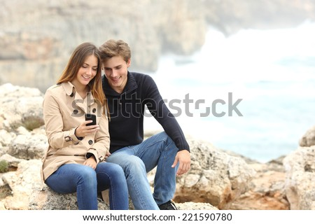 Couple sharing a smart phone on the beach on winter holidays with the ocean in the background - stock photo