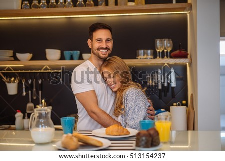 Couple sharing affectionate moment while having breakfast together at home.