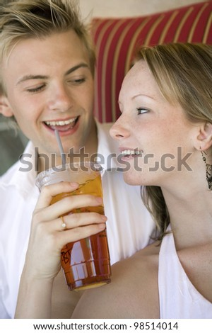 Couple Sharing Drink Poolside