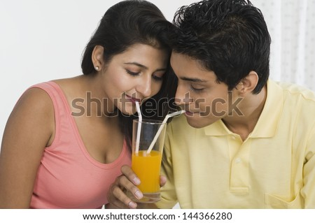 Couple sharing juice from a glass - stock photo