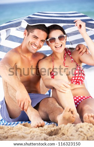 Couple Sheltering From Sun Under Beach Umbrella - stock photo