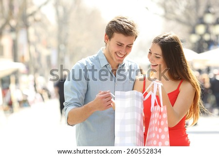 Couple shopping and holding bags while watching the products inside in the street