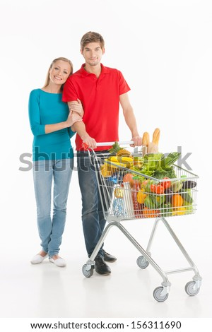 Couple shopping. Cheerful couple standing near shopping cart and smiling while isolated on white