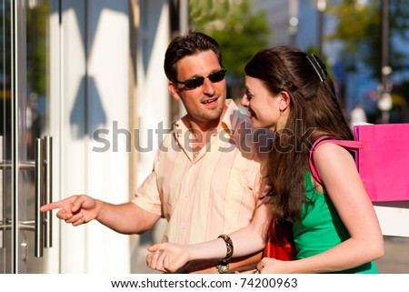 Couple shopping downtown with colorful shopping bags, they are lolling into a glass store door - stock photo