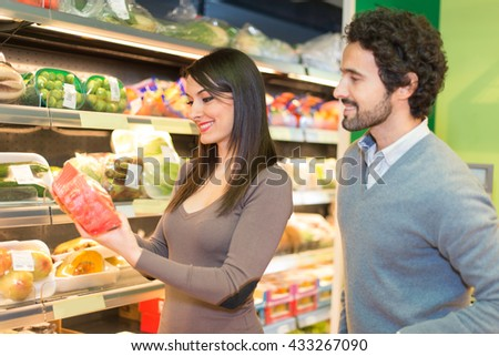 Couple shopping in a supermarket. The woman is reading a label