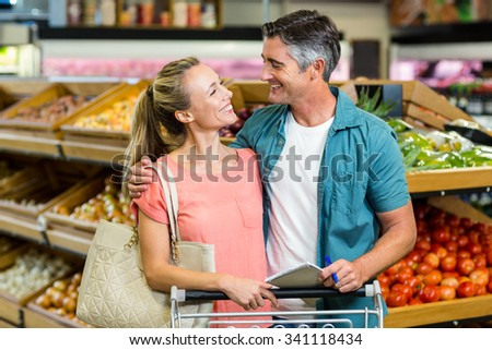 Couple shopping in grocery store and smiling to each other - stock photo