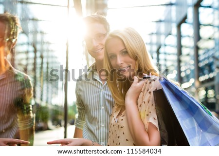 Couple shopping in the free time in the sun with shopping bag - stock photo