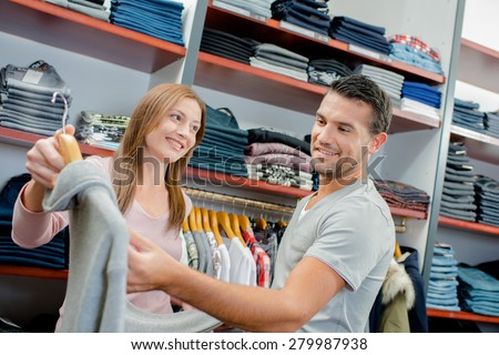 Couple shopping, man looking at price tag - stock photo