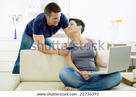 Couple shopping on internet paying by credit card. - stock photo