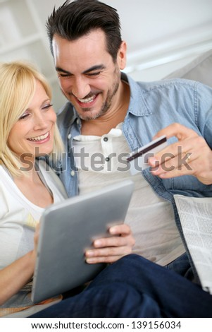 Couple shopping on internet with credit card - stock photo