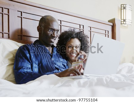 Couple shopping online in bed - stock photo
