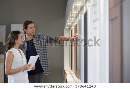 Couple shopping viewing samples in modern kitchen showroom looking at different finishes of cabinets cupboards - stock photo