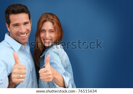 Couple showing thumbs up on blue background - stock photo