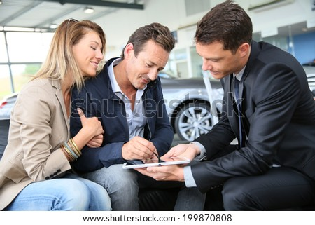 Couple signing car purchase order on digital tablet - stock photo