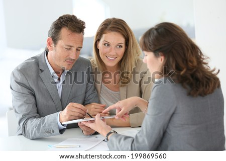 Couple signing loan grant on digital tablet - stock photo