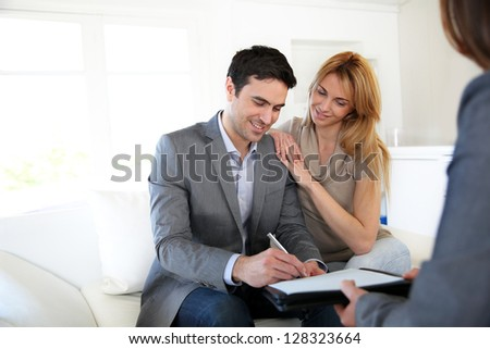 Couple signing terms of real-estate contract - stock photo