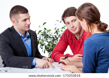 Couple signing the unfair mortgage agreement - stock photo