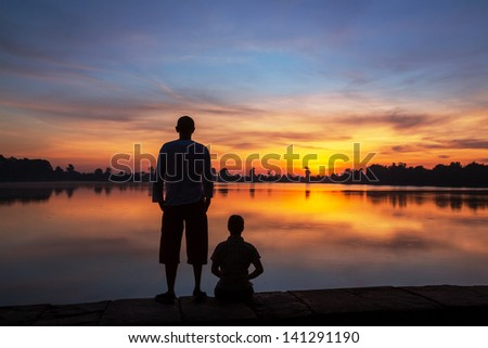 couple silhouette at sunset - stock photo