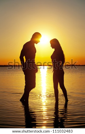 Couple silhouette at the beach at sunset.