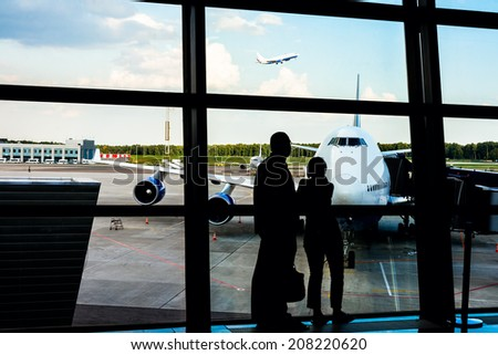 Couple silhouette looking through airport window to airplane