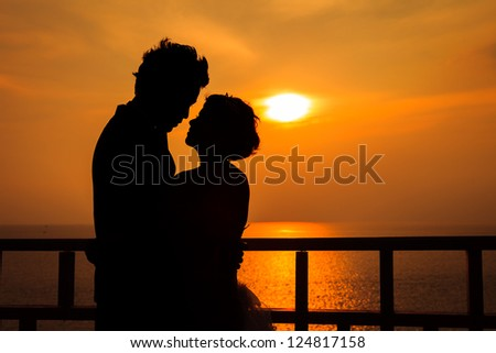 Couple silhouette on the beach at sunset - stock photo