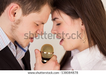 Couple singing a song together. Man and woman singing in microphone