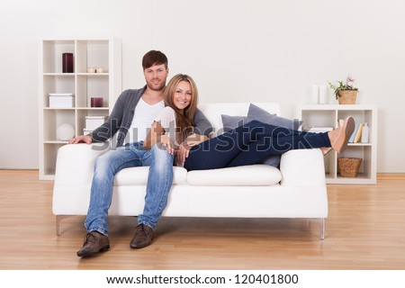 Couple sit on new couch bought at furniture shop. - stock photo