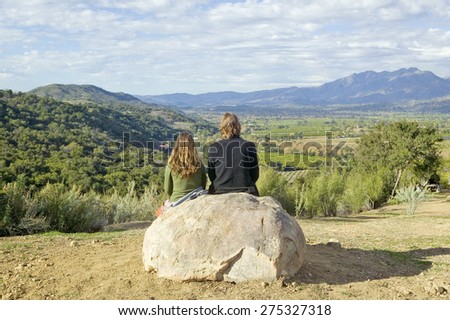 Couple sits and meditates at Meditation Mount's Point overlooking the Ojai Valley, CA - stock photo
