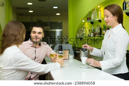 Couple sitting at bar and female bartender pouring coffee. Focus on man - stock photo