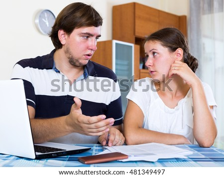 Couple sitting at desk with laptop, documents and counting budget