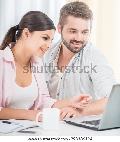 Couple sitting at home and using laptop together, drinking morning coffee.