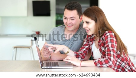 Couple sitting at table making online purchase using credit card