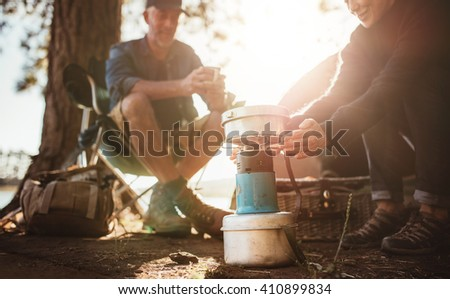 Couple sitting at the campsite on a sunny day, with woman warming her hands on camp stove. - stock photo
