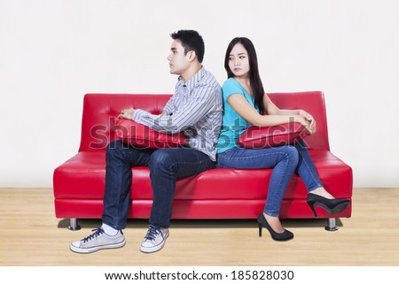 Couple sitting back to back after a fight on the sofa - stock photo