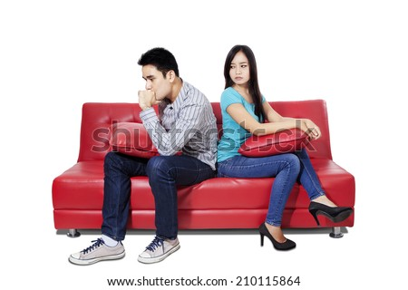 Couple sitting back to back after a fight on the sofa