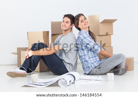 Couple sitting back to back in their new house - stock photo