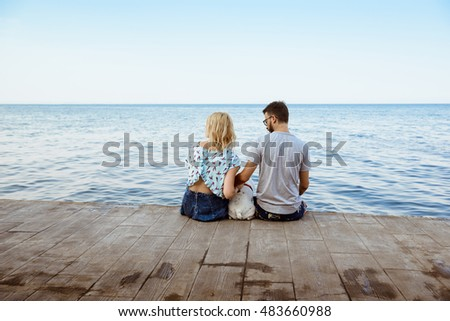 Couple sitting back to camera with French bulldog near sea.