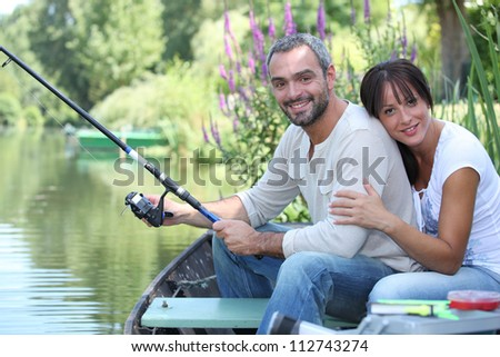 Couple sitting in a boat fishing - stock photo
