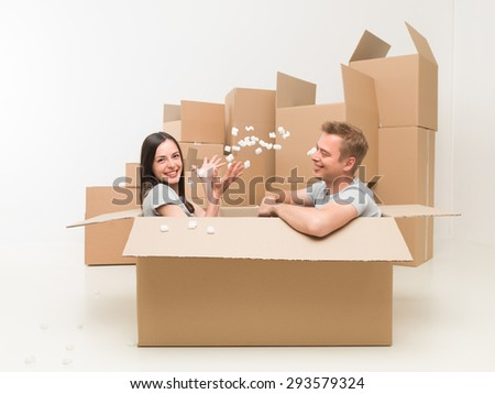 couple sitting in a box playing with packing material, having fun after moving in new home - stock photo