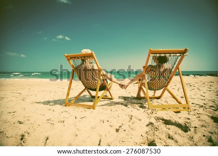 Couple sitting in beach chairs and holding hands on a tropical beach  - retro style background - stock photo