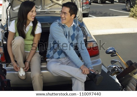 Couple sitting in car's trunk tying shoe lace getting ready to play golf - stock photo