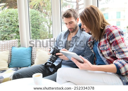 Couple sitting in coffee shop watching photos - stock photo