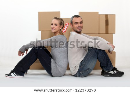Couple sitting in front of cardboard boxes - stock photo