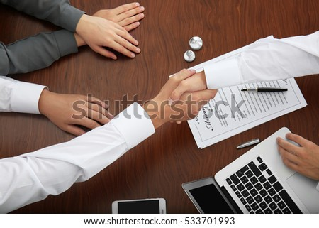 Couple sitting in notary public office and signing marriage documents