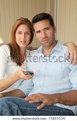 Couple sitting in sofa with tv remote control - stock photo