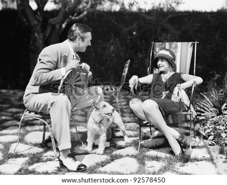 Couple sitting in the back yard talking with a dog between them - stock photo