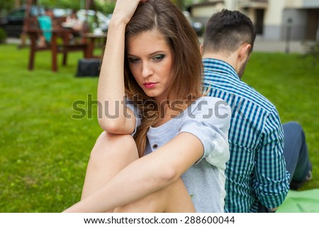 Couple sitting in the garden on the blanket back to back and girl  is sad - stock photo
