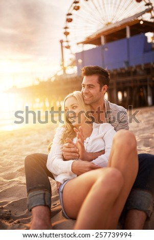 couple sitting in the sand on the beach near santa monica pier in california usa at sunset with bright golden lens flare - stock photo
