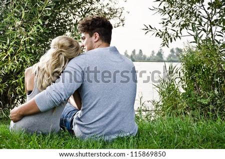 couple sitting on a beach in the meadow - stock photo