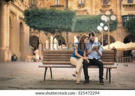 Couple sitting on a bench - stock photo